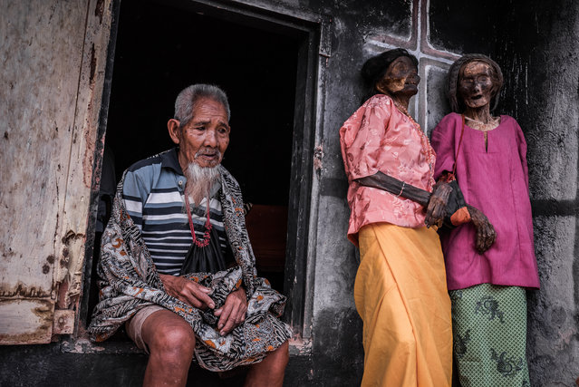 This picture shows Ne Duma Tata waiting to return his deceased wife to the mausoleum. Ludia Rante Bua (right) died in 2010. She stands alongside her sister. (Photo by Claudio Sieber Photography/The Guardian)
