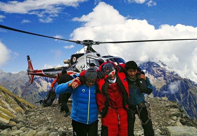 A man injured in an avalanche is rescued at the base camp of Mount Manaslu in northern Nepal, on September 23, 2012.  The avalanche swept away climbers on a Himalayan peak leaving at least nine dead and six others missing. (Photo by Simrik Air)
