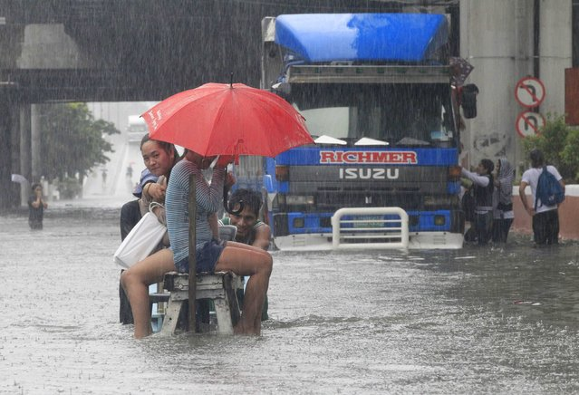 Stranded passengers ride on a improvised pushcart to cross a flooded street during tropical storm Fung-Wong in St Mesa, metro Manila September 19, 2014. (Photo by Erik De Castro/Reuters)