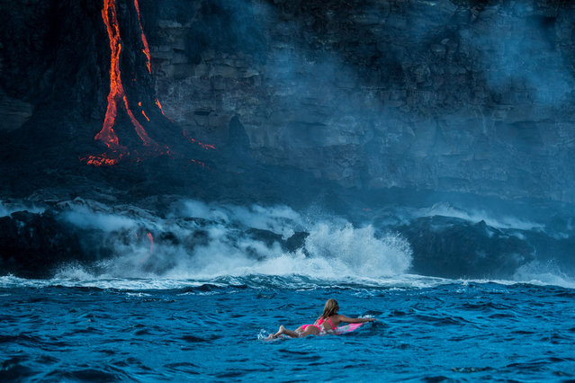 Alison Teal paddles out to Kilauea volcano in Hawaii as it eruopts into the ocean. (Photo by Perrin James/Caters News)