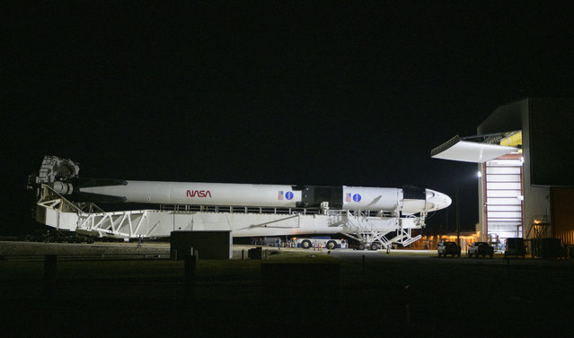 A SpaceX Falcon 9 rocket with the company's Crew Dragon spacecraft is rolled out of the horizontal integration facility at Launch Complex 39A as preparations continue for the Demo-2 mission, Thursday, May 21, 2020, at NASA's Kennedy Space Center in Cape Canaveral, Fla. (Photo by Bill Ingalls/NASA via AP Photo)