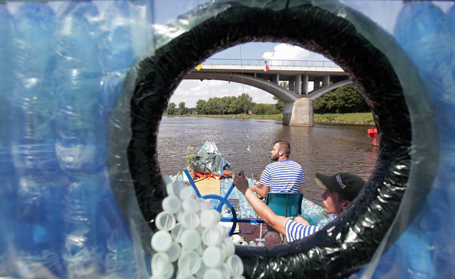 Jakub Bures (R) and Jan Holan are seen through a cabin window as they pedal their boat, made with plastic bottles, on the Elbe river near Kostelec nad Labem July 15, 2014. (Photo by David W. Cerny/Reuters)