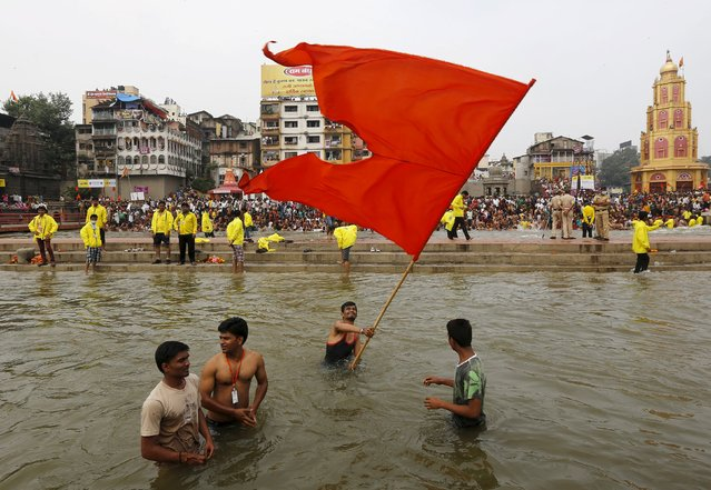 "A Hindu devotee waves a religious flag as others take a dip in the waters of Godavari river during the second ""Shahi Snan"" (grand bath) at Kumbh Mela or Pitcher Festival in Nashik, India, September 13, 2015. (Photo by Adnan Abidi/Reuters)"