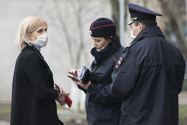 In this April 8, 2020, file photo, police officers check documents of a woman to ensure she is complying with a self-isolation regime due to the coronavirus in Moscow, Russia. A smartphone app designed to track Moscow's quarantined patients was rolled out by city officials in early April, but complaints about it have mushroomed, with users saying the software is full of glitches and has imposed unwarranted fines on them. (Photo by Pavel Golovkin/AP Photo)