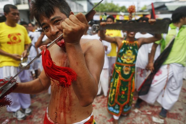 Devotees of the Chinese Bang Neow Shrine cut themselves with swords and other sharp objects during a procession celebrating the annual vegetarian festival in Phuket September 29, 2014. (Photo by Damir Sagolj/Reuters)
