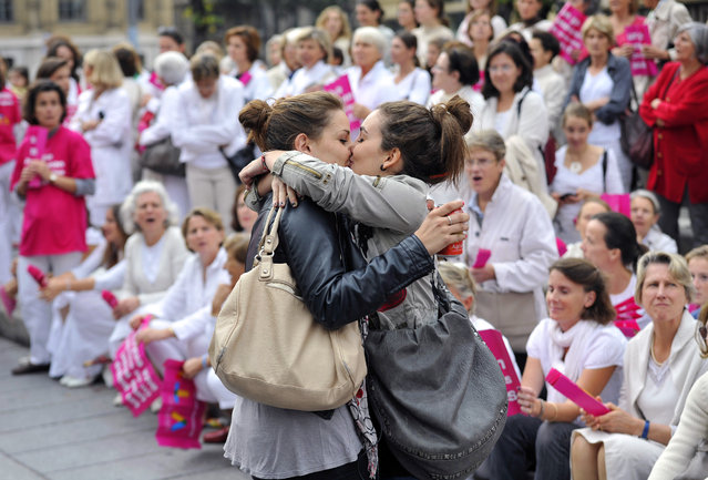 """Two women kiss in front of people taking part in a demonstration called by the """"Alliance VITA"""" association against gay marriage and adoption by same-s*x couples on October 23, 2012 in Marseille, southeastern France. France on October 10 named October 31 as the date when a draft law authorising gay marriage will be approved by government ministers, amid mounting opposition to the proposed legislation. (Photo by Gerard Julien/AFP Photo)"""