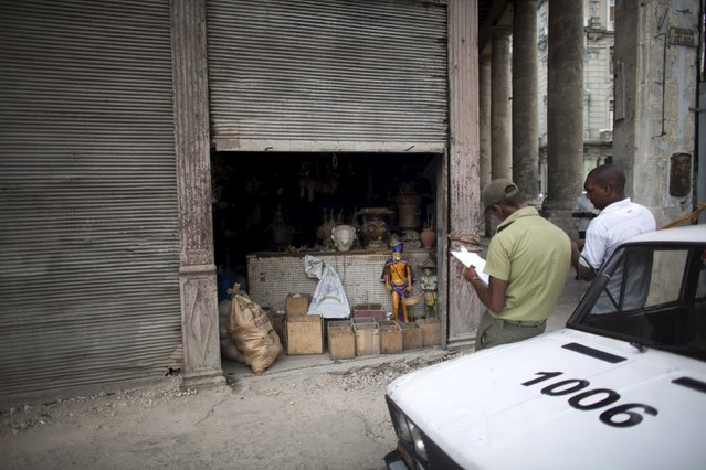 Police officers check a recently robbed shop of Santeria articles in downtown Havana, August 21, 2015. (Photo by Alexandre Meneghini/Reuters)