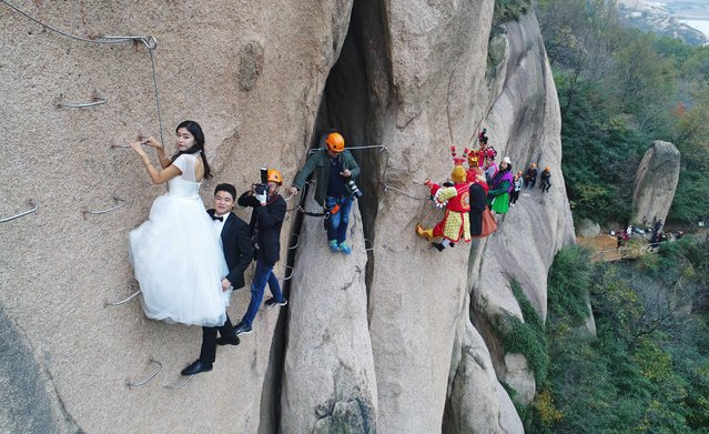 A newlywed couple dangling from a cliff face poses for wedding photos at the Chaya Mountain scenic spot on November 11, 2017 in Zhumadian, Henan Province of China. (Photo by Sipa Asia/Rex Features/Shutterstock)