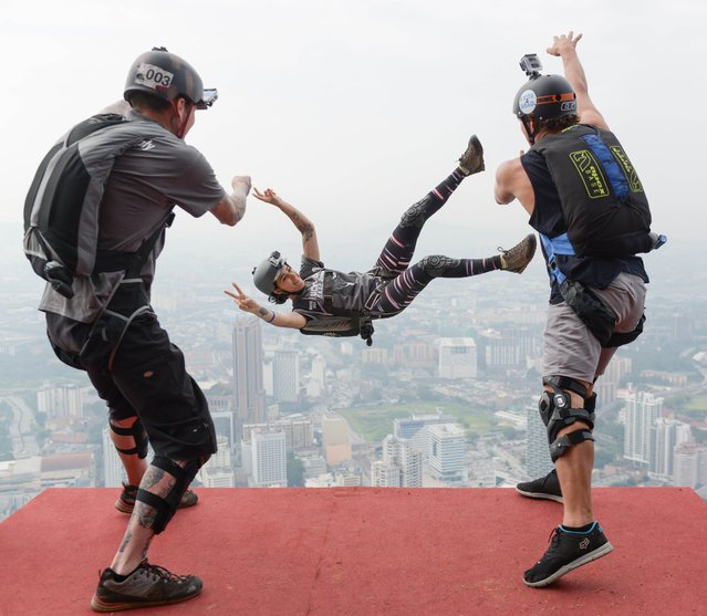 Base jumpers Alex Edge of the US (L) and Jeff Weatherall of New Zealand (R) throw Clair Marie of the US (C) on her birthday from the 300-metre high Open Deck of Malaysia's landmark Kuala Lumpur Tower during the International Tower Jump in Kuala Lumpur on September 27, 2014. Some 100 professional base jumpers from 20 countries are taking part in the annual event. (Photo by Mohd Rasfan/AFP Photo)