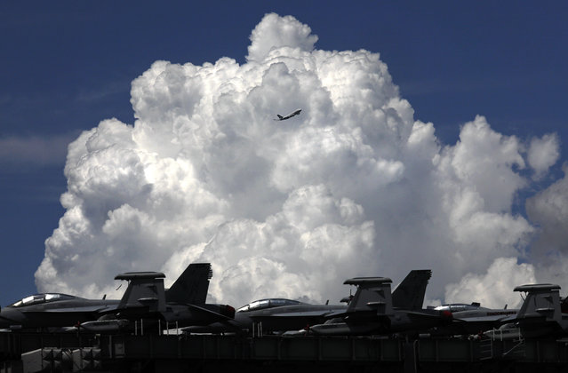 A commercial plane flies over the USS Ronald Reagan aircraft carrier in Hong Kong, Monday, October 2, 2017. A senior U.S. Navy commander of the nuclear powered aircraft carrier reportedly participating in joint drills with South Korea later this month told reporters during a stop in Hong Kong on Monday that his strike group is committed to defending U.S. allies in the region. (Photo by Vincent Yu/AP Photo)