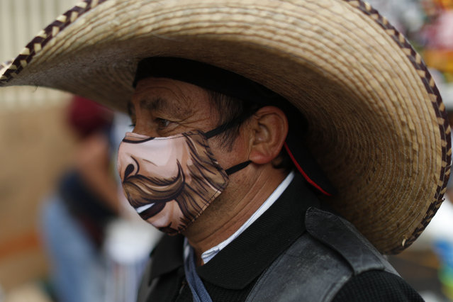 A man wearing a face mask walks amidst outdoor stalls at Mercado Sonora, which reopened ten days ago with measures to reduce congestion and limit the spread of the coronavirus, in Mexico City, Thursday, June 25, 2020. (Photo by Rebecca Blackwell/AP Photo)