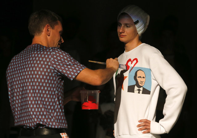 "Artist Alexey Sergienko (L) paints a heart on a shirt during a presentation of the fashion brand ""Homeland"", which was held on Russian President Vladimir Putin's 62nd birthday anniversary, in St. Petersburg, October 7, 2014. (Photo by Alexander Demianchuk/Reuters)"
