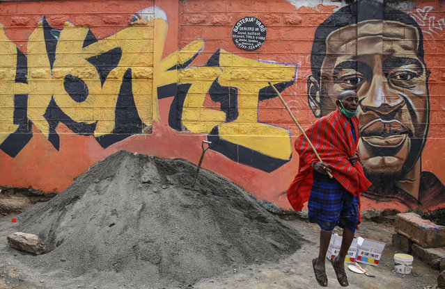 """In this Wednesday, June 3, 2020, file photo, a Maasai man jumps next to a new mural painted this week in the Kibera slum of Nairobi, Kenya, showing George Floyd with the Swahili word """"Haki"""" or """"Justice"""". Floyd's killing in the United States has raised awareness over police violence in South Africa and Kenya. (Photo by Brian Inganga/AP Photo/File)"""