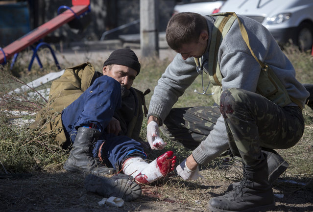 A pro-Russian rebel injured by shrapnel gets a field dressing after action near to the airport in the town of Donetsk, eastern Ukraine Tuesday, October 7, 2014.  (Photo by Dmitry Lovetsky/AP Photo)