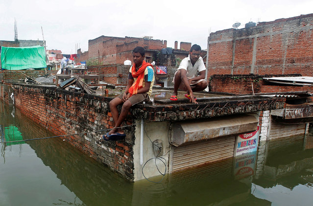 Men sit on the roof of a partially submerged shop in a flooded residential colony in Allahabad, August 23, 2016. (Photo by Jitendra Prakash/Reuters)
