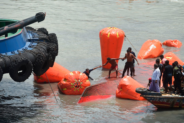 "Rescue and fire service personnel carry on rescue works the day after a ferry capsized in the Buriganga River in Dhaka on June 30, 2020. At least 32 people died after a ferry capsized and sank on June 29 in the Bangladeshi capital Dhaka following a collision, said rescuers, who found one man alive in a ""miracle"" hours later. A dozen people were initially listed as missing. (Photo by Munir Uz Zaman/AFP Photo)"