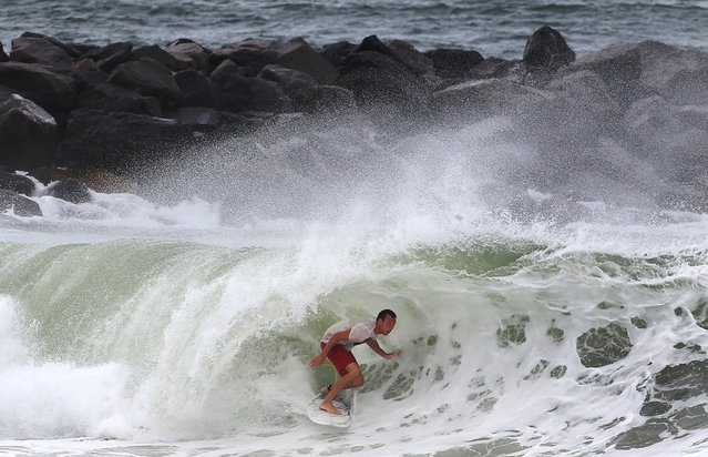 """A surfer gets into the tube while surfing the swell from Tropical Storm Hermine at St. Andrews State Park in Panama City Beach, Fla., on Thursday, September 1, 2016. Residents and businesses along Florida's Gulf coast put up shutters, nailed plywood across storefronts and braced Thursday for Tropical Storm Hermine, a system the governor called potentially """"life-threatening"""" likely to become the first hurricane to strike the state in over a decade. (Photo by Andrew Wardlow/The News Herald via AP Photo)"""