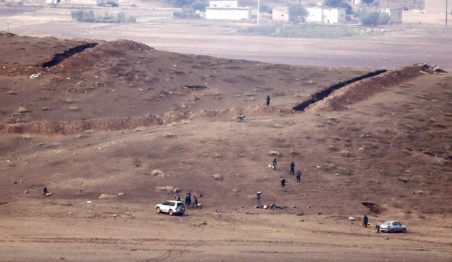 Kurdish fighters from the Syrian town of Kobani walks torwards trenches near the Mursitpinar border crossing on the Turkish-Syrian border in the southeastern town of Suruc in Sanliurfa province, October 17, 2014. (Photo by Kai Pfaffenbach/Reuters)