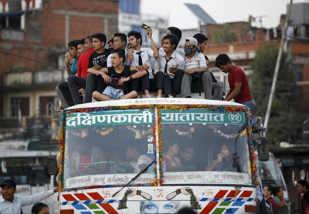 Passengers take a ride on an overcrowded bus as limited public transportation operates in the city during the ongoing crisis on oil and fuel in Kathmandu, Nepal September 29, 2015. (Photo by Navesh Chitrakar/Reuters)