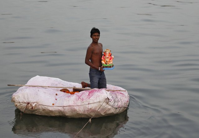 A boy holds an idol of the Hindu god Ganesh, the deity of prosperity, on a makeshift raft to immerse it in the waters of the river Sabarmati during the ten-day-long Ganesh Chaturthi festival in Ahmedabad, India, September 23, 2015. (Photo by Amit Dave/Reuters)