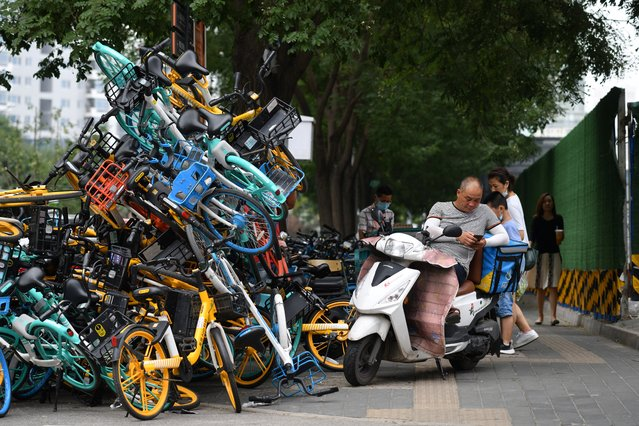 A delivery rider rests on a scooter next to a stack of shared bicycles on a sidewalk in Beijing on July 30, 2020. (Photo by Greg Baker/AFP Photo)