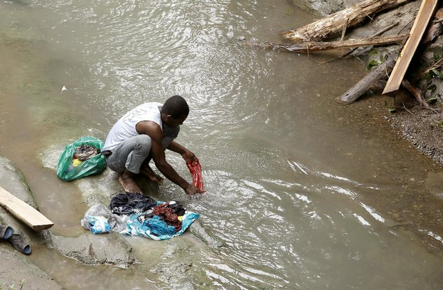 An African migrant stranded in Costa Rica washes their clothes in a river at the border between Costa Rica and Nicaragua, in Penas Blancas, Costa Rica,  September 8, 2016. (Photo by Juan Carlos Ulate/Reuters)