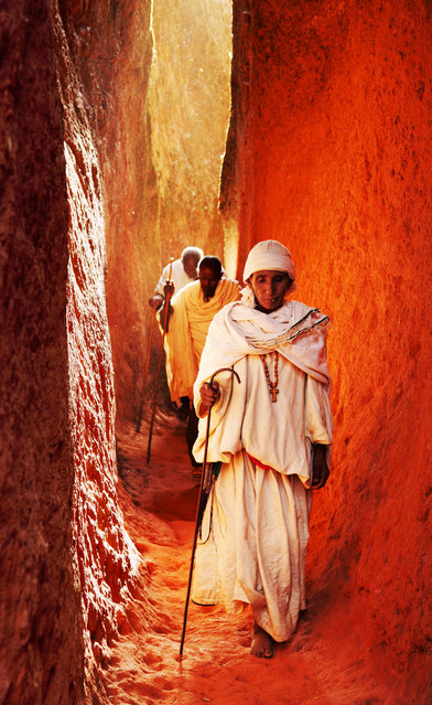 """""""Pilgrims"""". In Lalibela Ethiopia, pilgrims make their way through a narrow passageway carved into the rock leading to one of the many beautiful churches in the area. Just before the Orthodox Christian Christmas, thousands of people come from all over the countryside to gather and pray at the amazing stone carved churches. Photo location: Lalibela, Ethiopia. (Photo and caption by Bjoern Obst/National Geographic Photo Contest)"""