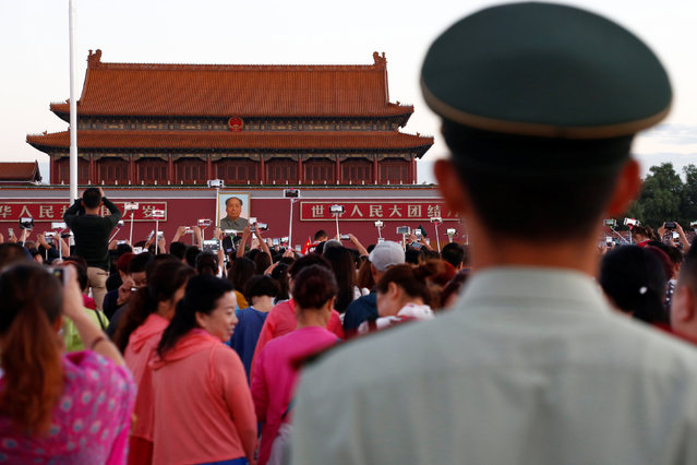 People take pictures during the flag raising ceremony on Tiananmen Square as the portrait of China's late Chairman Mao Zedong is seen in the background in Beijing, China, on the 40th anniversary of his death September 9, 2016. (Photo by Thomas Peter/Reuters)