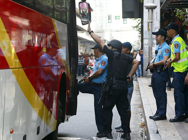 Policemen stand guard near the bus door during a robbery incident inside a public bus in Manila October 8, 2015. (Photo by Romeo Ranoco/Reuters)