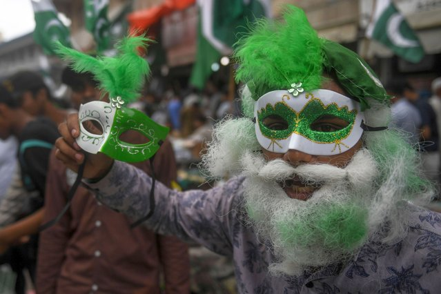 A vendor wearing a mask with the colours of Pakistan's national flag holds another mask while waiting for customers at a market in Karachi on August 12, 2020, ahead of the country's 74th Independence Day, which marks the end of British colonial rule, on August 14. (Photo by Asif Hassan/AFP Photo)