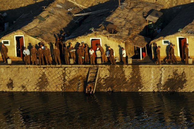 """""""Soldier-builders"""" perform their morning activities on banks of Taedong River in Pyongyang, North Korea early October 9, 2015. (Photo by Damir Sagolj/Reuters)"""