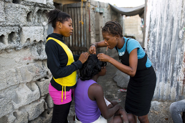 A woman does her neighbor's hair in the Cite Soleil slum of Port-au-Prince, Haiti, on December 27, 2017. (Photo by Dieu Nalio Chery/AP Photo)