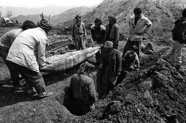 Iraqi Kurdish men bury the dead in Cukurca refugee camp in Turkey April 8, 1991. (Photo by Srdjan Zivulovic/Reuters)