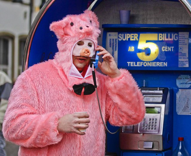 """A man dressed as a pig uses a phone during the start of the street-carnival with its tradition of fools entering the town halls and women cutting off men's ties with scissors on carnival's so called """"Old Women's Day"""" in Cologne, Germany, on February 7, 2013. (Photo by Frank Augstein/Associated Press)"""