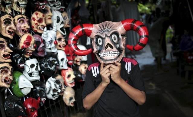 A child tries on masks before the Los Aguizotes festival in the indigenous community of Monimbo in Masaya, Nicaragua, October 16, 2015. (Photo by Oswaldo Rivas/Reuters)