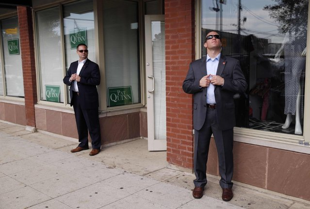 Secret Service agents keep watch as U.S. President Barack Obama visits a Pat Quinn campaign office in Chicago in this October 20, 2014 file photo. Two agents were posted outside this generic campaign office, and the simplicity of the setting and placement of the agents caught my eye. I took about 10 frames, and then one agent looked up. The juxtaposition of the agents was visually interesting and unique to me. (Photo and caption by Kevin Lamarque/Reuters)