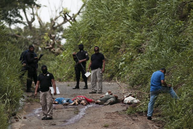 Police and investigators work at a crime scene where four men were executed in the town of Cojutepeque, El Salvador, October 21, 2015. (Photo by Jose Cabezas/Reuters)