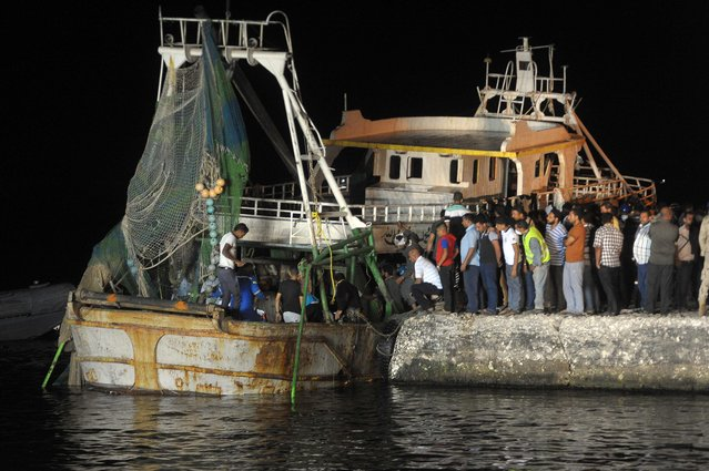 People gather on the quay as a wreck of a migrant boat raised by the Egyptian navy and maritime rescuers arrives in the Egyptian port city of Rosetta on September 27, 2016. The Egyptian military said 163 people had been rescued. The boat would have had at least 365 people on board when it went down en route to Italy, according to official figures. (Photo by AFP Photo/Stringer)