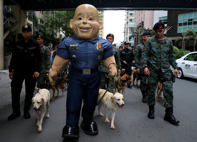 A mascot of the Philippine National Police (PNP), named after their Chief Director General Ronald Dela Rosa, marches with members of the K9 units and the Special Action Force before the mass blessing for rescue dogs during the celebration of the feast day of St. Francis of Assisi, patron Saint of Animals, at the St. John Paul II parish church in Eastwood, Quezon city, metro Manila, Philippines October 2, 2016. (Photo by Romeo Ranoco/Reuters)