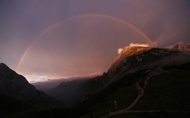 A rainbow spans over the Hohes Goell (L) and Schneibstein mountains near the Carl-von-Stahl-Haus Alpine Club hut in the Berchtesgaden, Bavaria, Alpine region near the Austrian-German border August 1, 2014. (Photo by Wolfgang Rattay/Reuters)