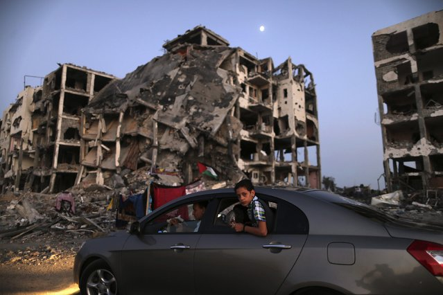 A Palestinian boy rides in a car driving past residential buildings in Beit Lahiya town, which witnesses said was heavily hit by Israeli shelling and air strikes during the Israeli offensive, in the northern Gaza Strip, in this August 7, 2014 file photo. (Photo by Mohammed Salem/Reuters)