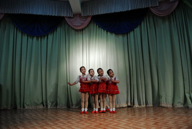 This picture taken on December 15, 2012 shows North Korean girls dancing during a performance at a nursery school in the North Korean border town of Siniuju, across from China's northeastern city of Dandong. (Photo by Wang Zhao/AFP Photo)
