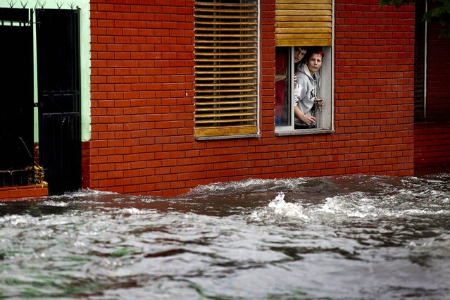 A couple looks at their flooded street from behind their home's window in La Plata, in Argentina's Buenos Aires province, where at least 35 people were killed by flooding overnight, on April 3, 2013. (Photo by Natacha Pisarenko/Associated Press)