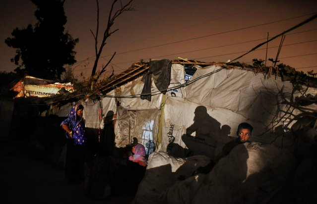 In this November 10, 2014 photo, Shahid-ul, 7, right, sits on a sack of trash as his mother Marjina, center, speaks to a neighbor outside their rented shanty on the outskirts of New Delhi, India. (Photo by Altaf Qadri/AP Photo)