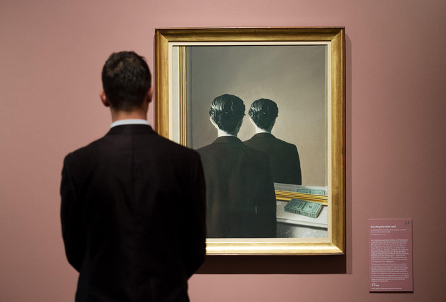 "In this October 5, 2016 photo a man looks at the work ""Not to be Reproduced"" by Rene Magritte at the Kunsthalle art gallery in Hamburg, Germany. The exhibition, which runs from Oct. 7,  2016 until Jan. 22,  2017, features more than 150 masterpieces of surrealism from four of the most significant European private collections of the 20th century. (Photo by Daniel Reinhardt/DPA via AP Photo)"