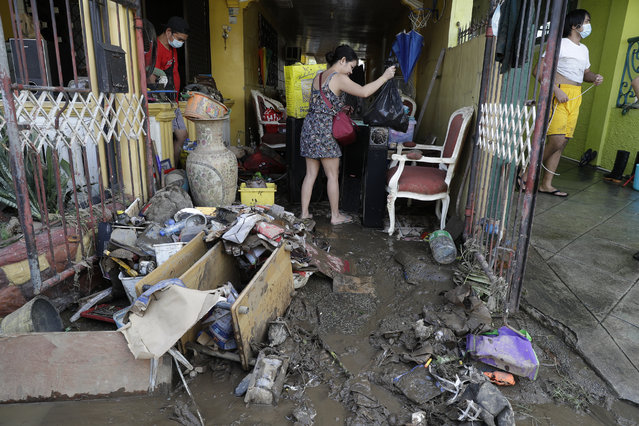 Residents try to save belongings after floodwaters caused by Typhoon Goni rose inside their village in Batangas city, Batangas province, south of Manila, Philippines on Monday, November 2, 2020. (Photo by Aaron Favila/AP Photo)