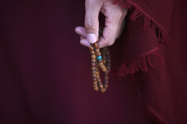 A Tibetan nun holds prayer beads during a function organised by the Tibetan Refugee Community in Nepal commemorating the 25th Anniversary of the Nobel Peace Prize conferment to exiled Tibetan spiritual leader Dalai Lama and the 66th International Human Rights Day in Kathmandu December 10, 2014. (Photo by Navesh Chitrakar/Reuters)