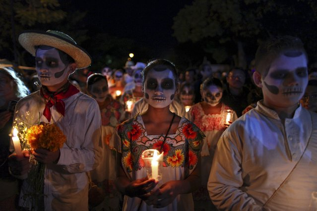 "People, with their faces painted as skulls, take part in a traditional parade called ""Paseo de las Animas"", or Parade of Souls, as part of Day of the Dead celebrations in Merida, Mexico, October 31, 2015. (Photo by Lorenzo Hernandez/Reuters)"