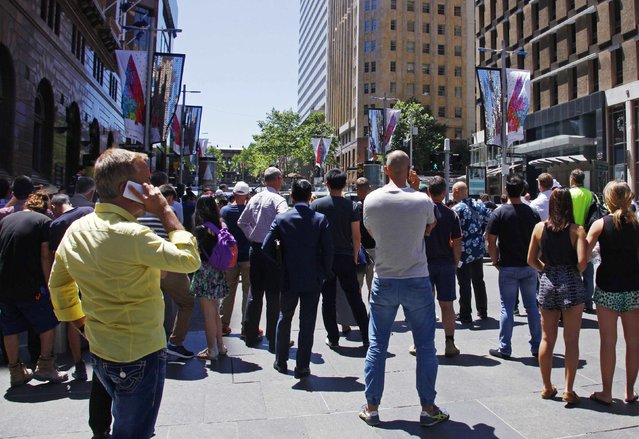 People standing behind a police cordon look towards Lindt cafe in Martin Place, where hostages are being held, in central Sydney December 15, 2014. (Photo by David Gray/Reuters)