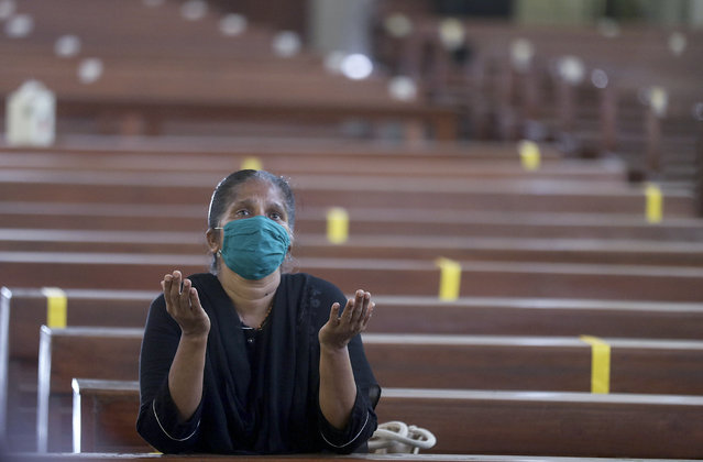 A Christian devotee wearing a mask offers prayers at a Church in Mumbai, India, Monday, November 16, 2020. Religious places across the Maharashtra state reopened for devotees on Monday after remaining closed due to the COVID-19 pandemic. A country of nearly 1.4 billion people, India is the world's second most coronavirus affected country after the United States. (Photo by Rafiq Maqbool/AP Photo)
